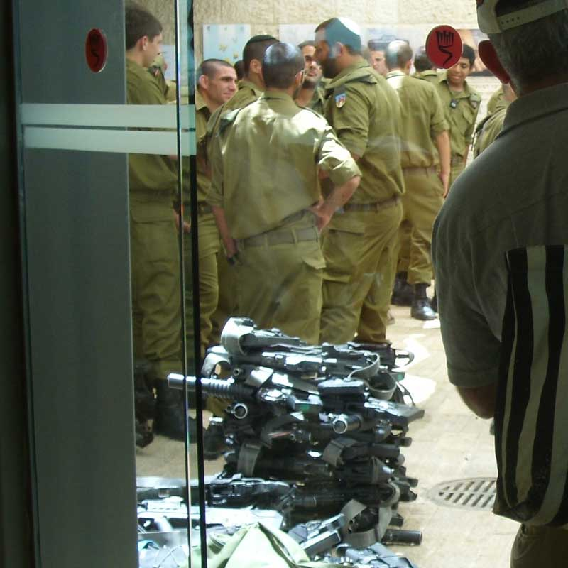 Guns at Yad Vashem: Young Israelis visit Yad Vashem, Israel's national Holocaust memorial, to complete their induction in the Israeli Army. They deposit their weapons at the entrance.  Image © Mike Joseph.